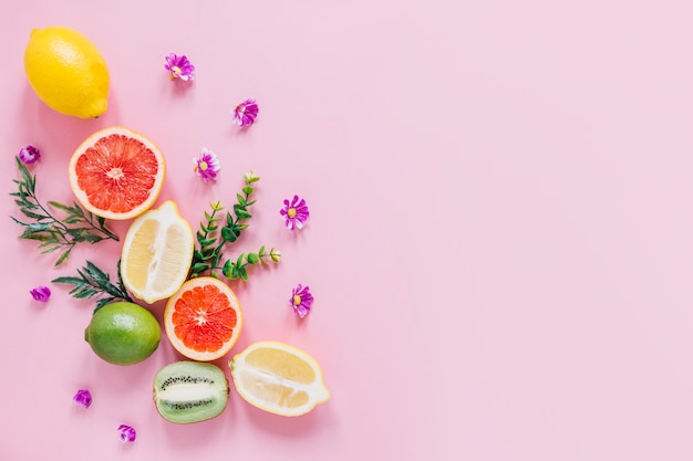 Kleine blumen und blätter in der nähe von zitrusfrüchten