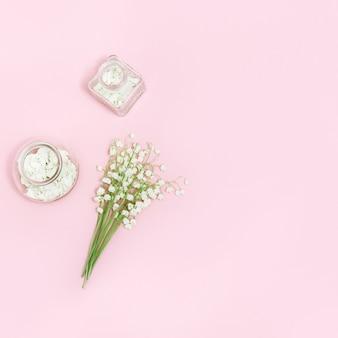 Kleine blumen von maiglöckchen und glasflasche mit trockenen blütenblättern auf zartem rosa hintergrund mit kopienraum für text. frühlingszeit und aromatherapie.