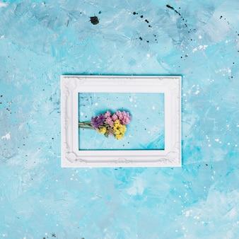 Kleine blumenniederlassungen im weißen rahmen auf tabelle