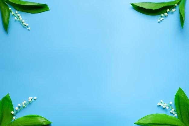 Kleine blumensträuße von maiglöckchen in den ecken mit kopienraum flach mit blauem hintergrund