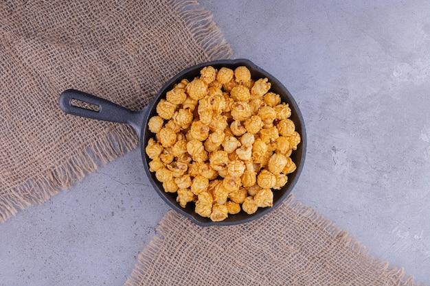 Kleine bratpfanne auf stoffstücken gefüllt mit kandiertem popcorn auf marmorhintergrund. foto in hoher qualität