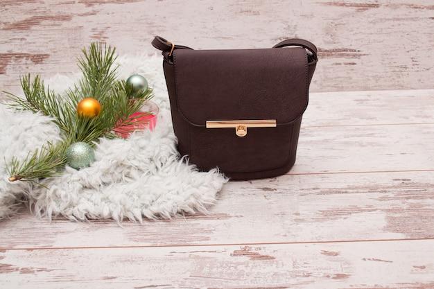 Kleine braune weibliche handtasche, tannenzweig mit dekorationen. fashion-konzept