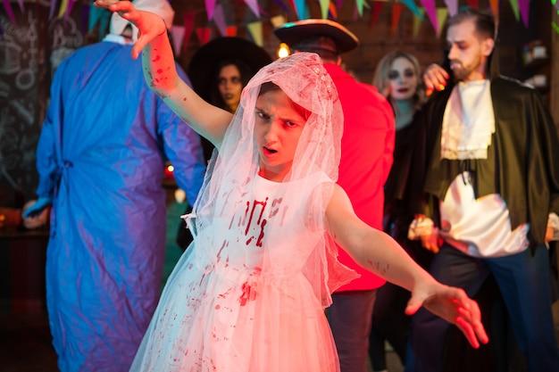 Kleine braut mit gruseligem gesicht, das bei halloween-party in die kamera schaut. dracula im hintergrund.