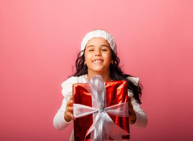 Kleine brünette mit langen haaren in einer wintermütze hält ein geschenk auf rosafarbenem hintergrund.