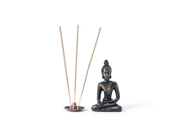 Kleine buddha-statue mit räucherstäbchen auf weißem hintergrund