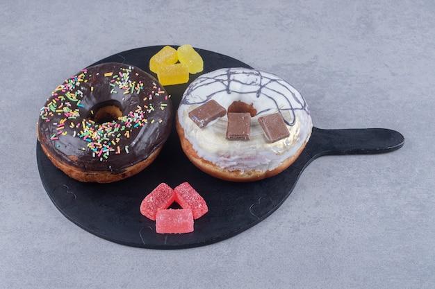 Kleine bündel marmeladen und zwei donuts auf einem tablett auf marmoroberfläche