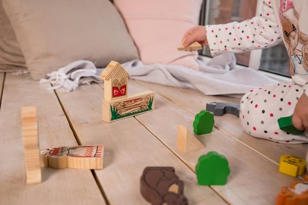 Kleine bunte hölzerne spielzeugformen und -bausteine auf massivholzboden mädchenspiel mit einem hölzernen satz in ihrem kinderzimmer auf dem boden. bunte blöcke auf dem boden.