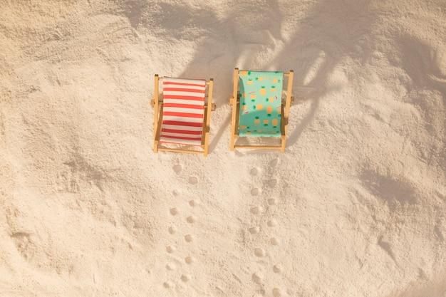 Kleine bunte liegestühle und fußabdrücke auf sand