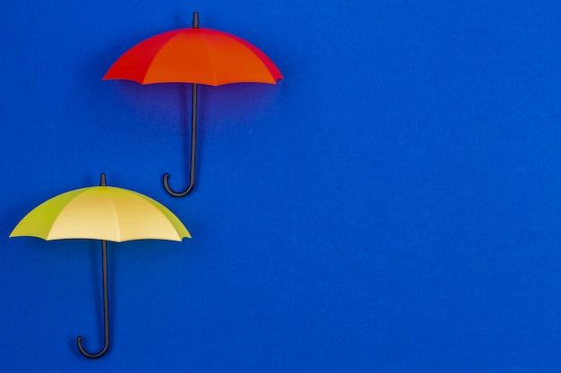 Kleine bunte regenschirme auf blauem farbhintergrund