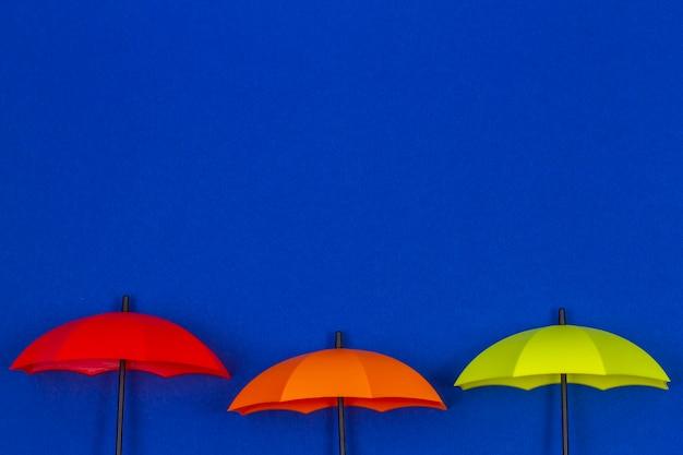 Kleine bunte regenschirme auf blauer farbe