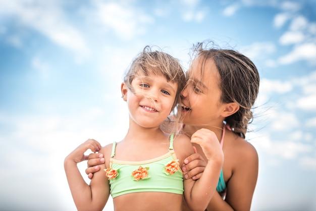 Kleine charmante schwestern flüstern an einem sommertag etwas