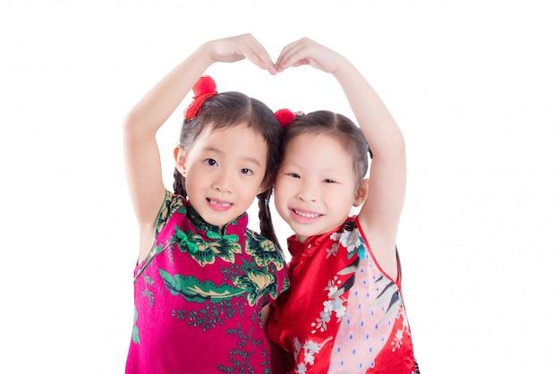 Kleine chinesische mädchen, die herzform tun
