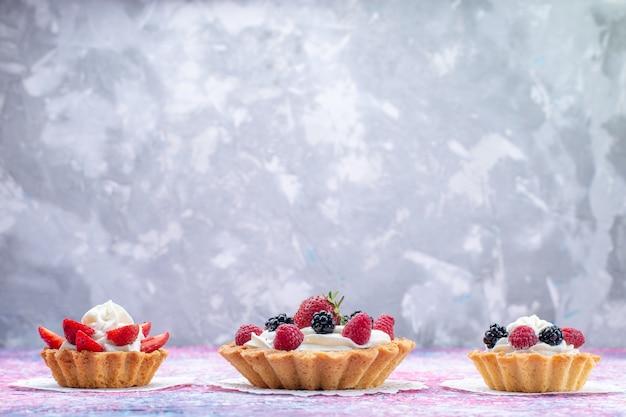 Kleine cremige kuchen mit beeren auf hellweißem, süßem kuchenfoto der kuchenkeksbeere