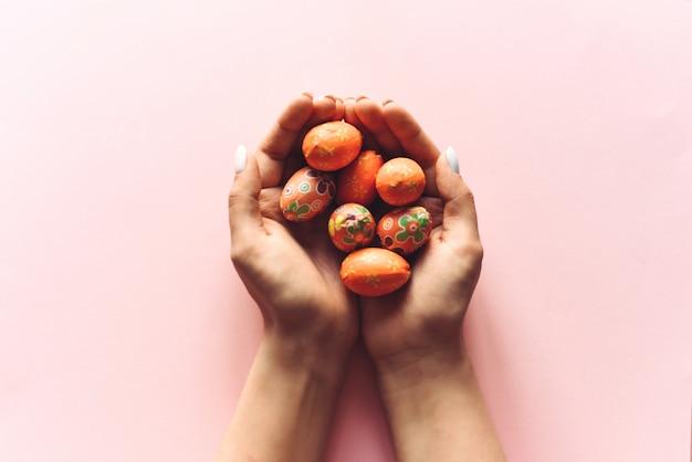 Kleine dekorative ostereier in den händen eines mädchens auf einem rosa hintergrund. schöne osterillustration