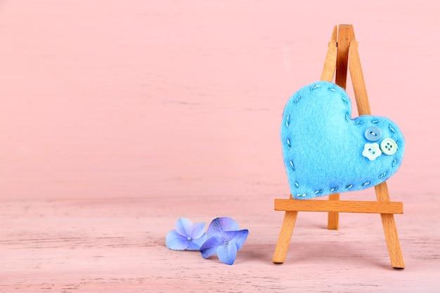 Kleine dekorative staffelei des schönen herzens auf rosa raum