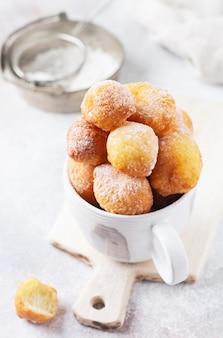 Kleine donuts. hausgemachte hüttenkäsekekse frittiert und mit puderzucker in einer vintage-keramikschale auf hellem hintergrund bestreut. selektiver fokus.