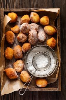 Kleine donuts. hausgemachte hüttenkäsekekse in tiefem fett gebraten und mit puderzucker in einem vintage holzkasten tablett gegen eine alte dunkelheit bestreut
