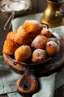 Kleine donuts. hausgemachte quark gebratene kekse in tiefem fett und bestreut mit puderzucker in einem vintage-teller auf hellem hintergrund. selektiver fokus