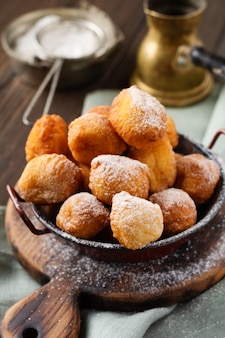 Kleine donuts. hausgemachte quark gebratene kekse in tiefem fett und mit puderzucker in einem vintage-teller bestreut