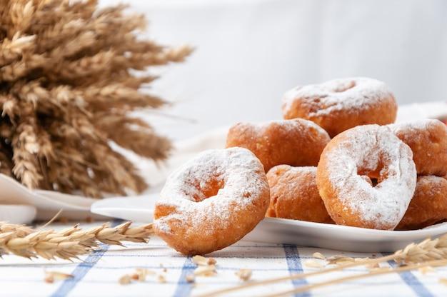 Kleine donuts mit puderzucker bestreut. auf einem weißen teller. im hintergrund weizenähren und körner.