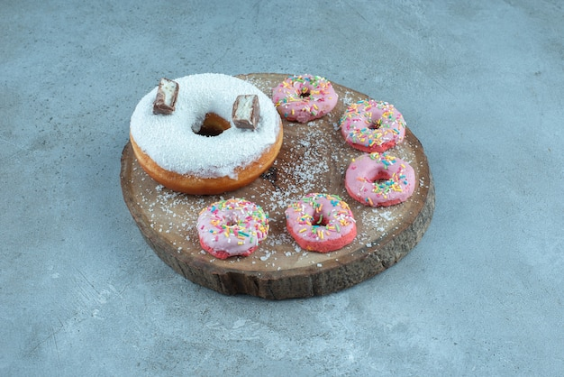 Kleine donuts um einen großen donut auf einem holzbrett auf marmor.