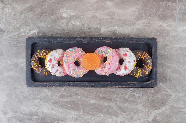 Kleine donuts und eine marmelade gebündelt auf einem schwarzen tablett auf marmoroberfläche