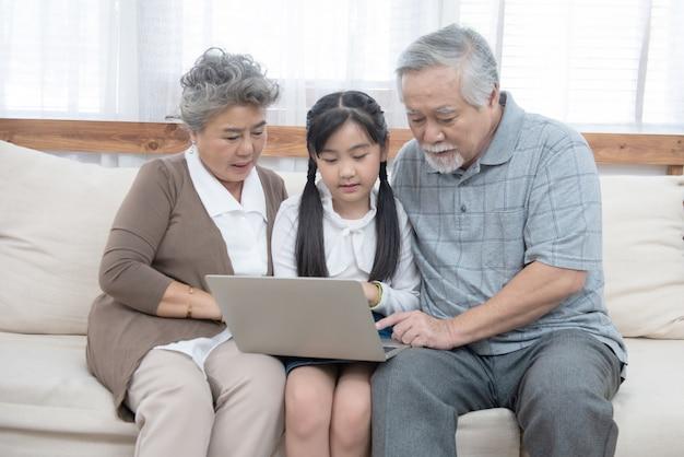 Kleine enkelin bringt älteren ältesten bei, mit computer und technologie und modernem lebensstil im internet zu surfen. glückliche asiatische großeltern mit dem kleinen jungen niedlichen enkelkind, das auf dem sofa sitzt und laptop spielt