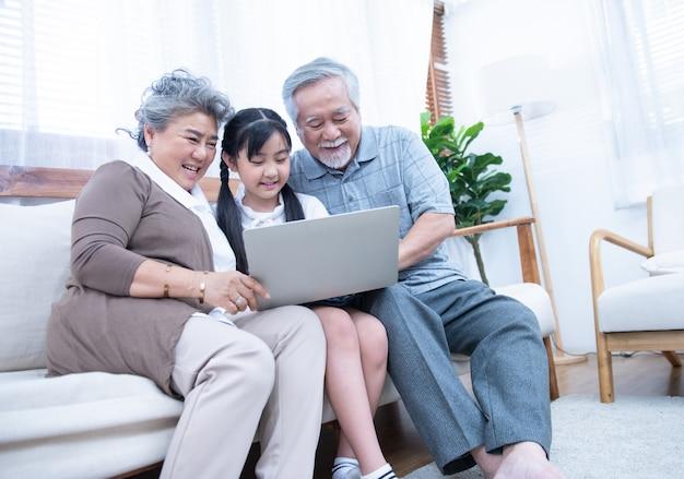 Kleine enkelin bringt älteren ältesten bei, mit einem laptop im internet zu surfen