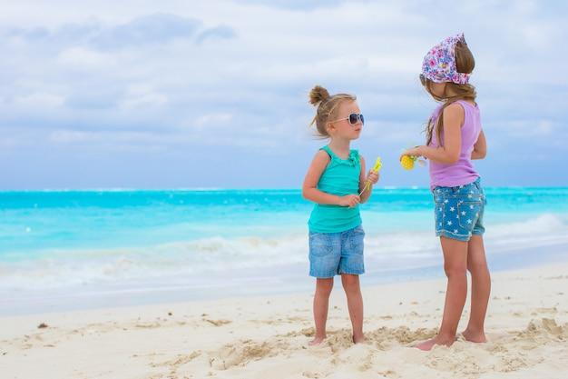 Kleine entzückende mädchen auf weißem tropischem strand
