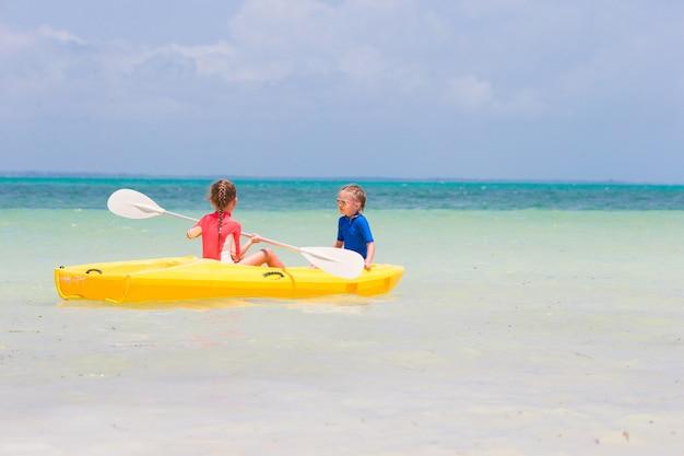 Kleine entzückende mädchen, die das kayak fahren auf gelbem kajak genießen