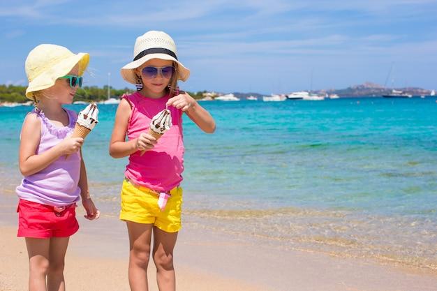 Kleine entzückende mädchen, die eiscreme auf tropischem strand essen