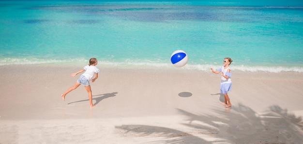 Kleine entzückende mädchen, die mit ball am strand spielen