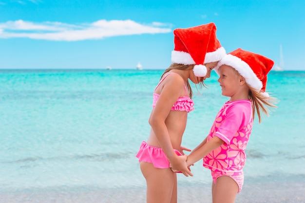 Kleine entzückende mädchen in santa hüte am strand