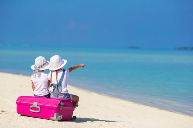 Kleine entzückende mädchen mit großem koffer auf tropischem weißem strand während der sommerferien