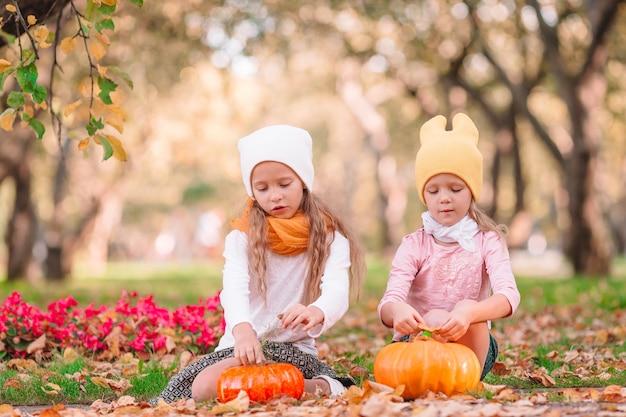 Kleine entzückende mädchen mit kürbis draußen an einem warmen herbsttag. porträt von kindern im herbst im oktober