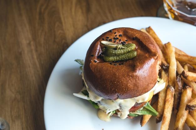 Kleine essiggurken oben auf einen mouthwatering rindfleischburger mit pommes-frites