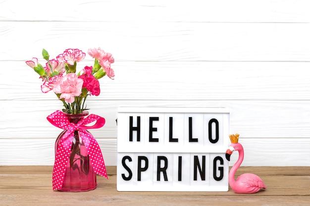 Kleine farbige rosa nelken in einer vase und lichtbox mit text hallo frühling, flamingofigur auf