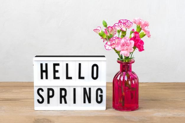 Kleine farbige rosa nelken in vase, leuchtkasten mit text hallo frühling, flamingofigur auf holztisch und grauer wand. hallo frühling