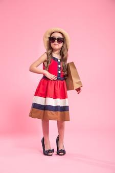 Kleine fashionista mit einer einkaufstasche in einem sommerhut und einer brille, auf einem farbigen rosa hintergrund in mamas schuhen, das konzept der kindermode