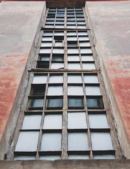 Kleine fenster in einem alten hochhaus gegen den hellen himmel