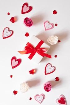 Kleine festliche geschenkbox mit roter schleife und verschiedenen arten von herzen. valentinstagskarte