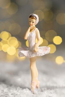 Kleine figur einer ballerina in einem weißen tutu auf dem schnee