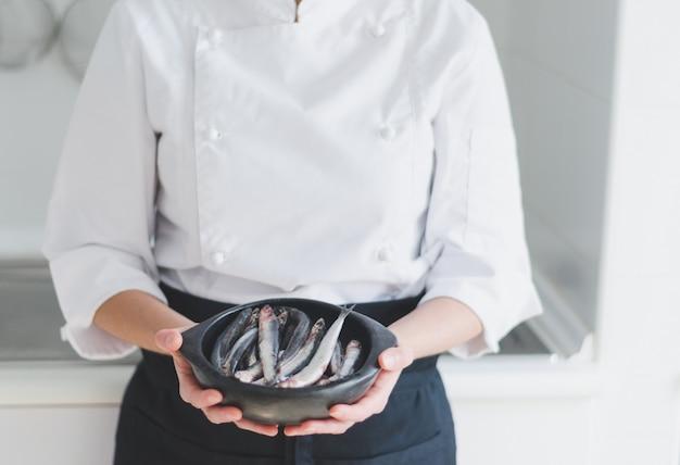 Kleine fische in der keramikschale über den händen des küchenchefs.