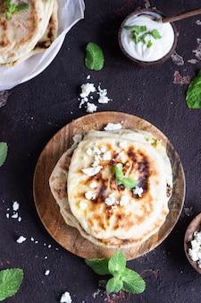 Kleine fladenbrote der zwiebel, der minze und des käses dienten auf einer hölzernen platte. gozleme.