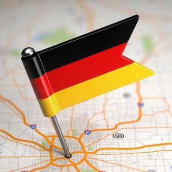 Kleine flagge der bundesrepublik deutschland auf kartenhintergrund mit selektivem fokus.