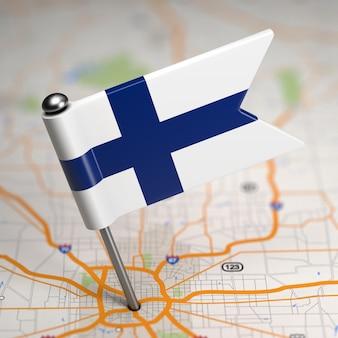Kleine flagge der republik finnland auf einem kartenhintergrund mit selektivem fokus.
