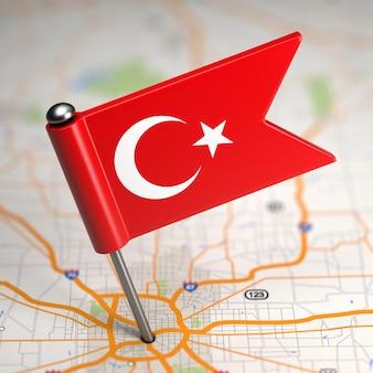 Kleine flagge der türkei auf einem kartenhintergrund mit selektivem fokus.