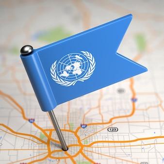 Kleine flagge der vereinten nationen auf einem kartenhintergrund mit selektivem fokus.