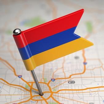 Kleine flagge republik armenien auf einem kartenhintergrund mit selektivem fokus.
