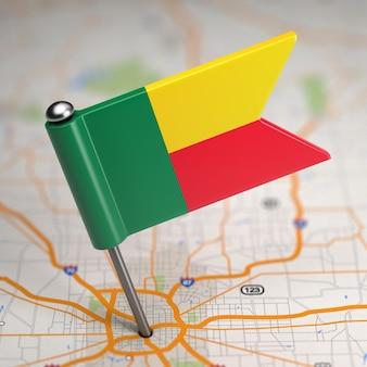 Kleine flagge republik benin auf einem kartenhintergrund mit selektivem fokus.